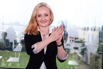 Junge Geschäftsfrau klatscht vor Begeisterung