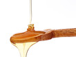 Dripping honey on wooden spoon