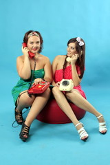 Two young women calling on phones on blue background