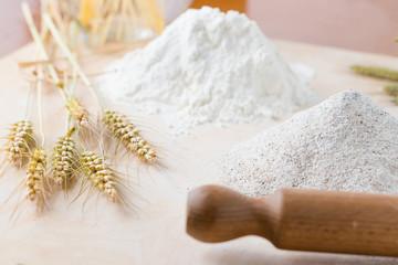 Farine bianche e spighe di grano su un asse di legno