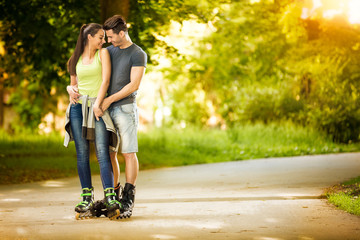 Love couple ride rollerblades in the park