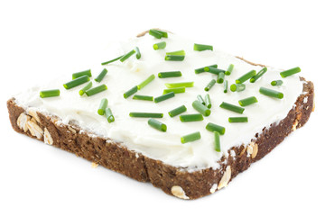 Cut fresh chives on thickly spread cream cheese on bread