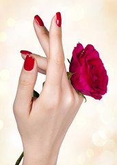 Red manicure on a woman's hand with red roses.