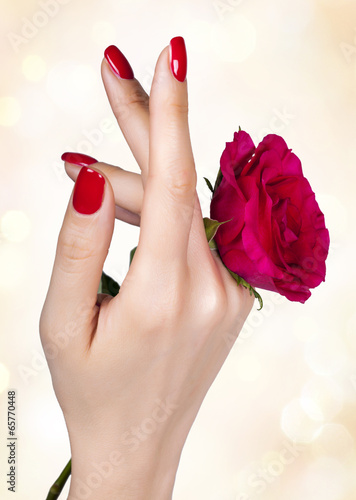 Red manicure on a woman's hand with red roses. Tableau sur Toile
