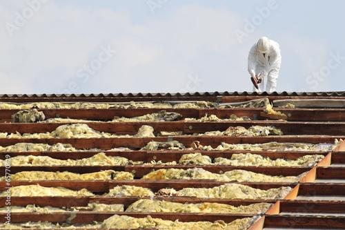 Arbeiter bei der Demontage/ Entsorgung von Dämmmaterial eins Daches - 65770629