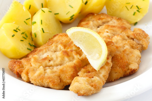 Golden fried schnitzel with boiled potatoes, chives and lemon.