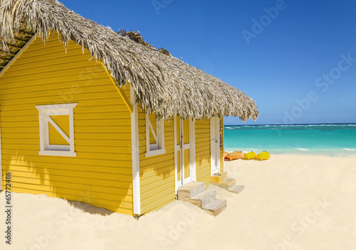 Leinwandbild Motiv Wooden yellow hut on the beach covered with thatch and kayaks