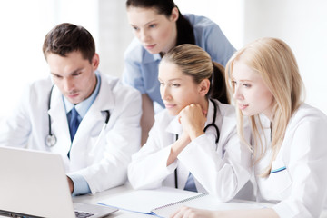 group of doctors looking at tablet pc