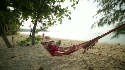 Woman reading on hammock by the beach