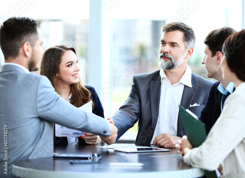 Business people shaking hands, finishing up a meeting  - 65774279