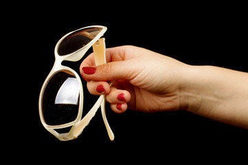Female hand holding stylish sunglasses on the black background