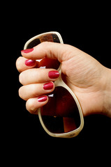 Female hand holding sunglasses on the black background
