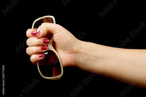 Female hand holding sun glasses