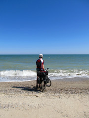 Man standing on the beach with bicycle.