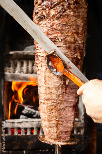 Doner meat being sliced from rotating spit - 65775223