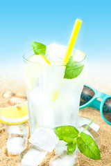 Cold water with lemon and ice on beach background