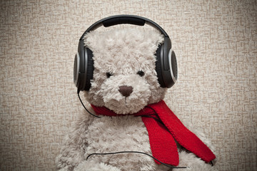 Toy teddy bear with a red scarf listening to music on headphones