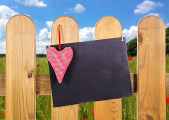 Gartenzaun mit Blankoschild und Herz