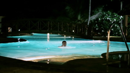 Man finish swimming in the pool at night