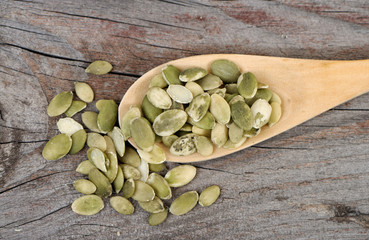 Pumpkin seeds in a wooden spoon. Top view.