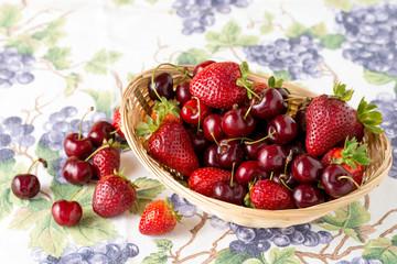 Cestino di vimini con fragole e ciliegie