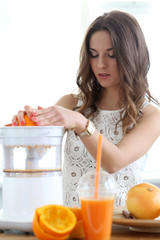 Beautiful girl making orange juice
