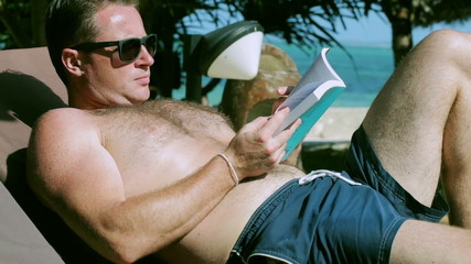 Man reading book on sunbed, steadycam shot