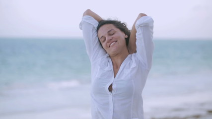 Happy woman standing on the beach, steadycam shot