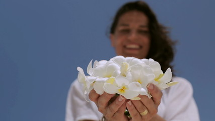 Woman holding white flowers and smiling