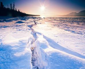 Sunny frozen Tagish Lake ice crack Yukon Canada