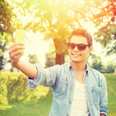 Young fashionable man with sunglasses taking a selfie outdoors