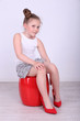 Beautiful small girl in big shoes sitting