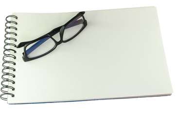 Pair of spectacles lying closed on a sketch book