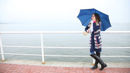 Woman with umbrella relaxing on the pier. Sea.