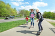 Family riding a skateboard and scooter