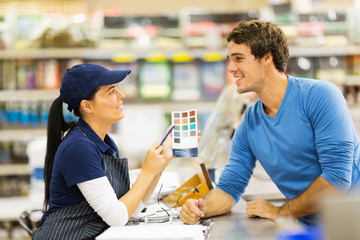 paint store assistant helping customer choose paint color