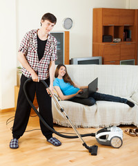 man doing house cleaning during girl resting