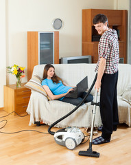 Man doing house cleaning with vaccuum cleaner