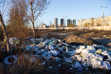 Garbage on the landfill near high-rise buildings of the city