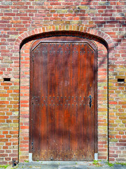 Restored wooden medieval door of church in bright day