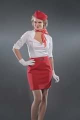 Smiling retro blonde stewardess wearing red skirt and cap with w