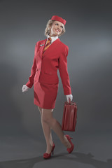 Smiling retro blonde stewardess wearing red suit with striped ti
