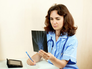 Young woman doctor examining an x-ray and writing, isolated