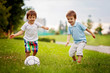 Two cute little boys, playing football