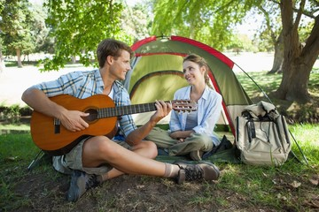 Cute man serenading his girlfriend on camping trip