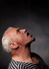 Portrait of a wet man on whom pours water