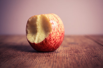 Half eaten apple on wooden table