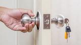 Hand holding door knob with keys