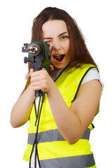 the girl in a construction vest an electric drill.