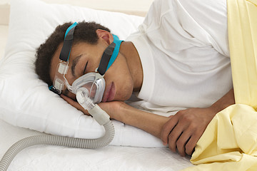 young mulatto man  sleeping with apnea and CPAP machine